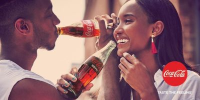 An African American man and women drink bottles of Coca-Cola while laughing at each other.